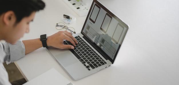 Młody profesjonalny programista interfejsu www pracujący nad aplikacją na smartfona z laptopem
