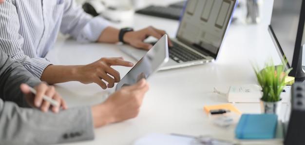 Młody profesjonalny programista interfejsu www pracujący nad swoim projektem z laptopem i tabletem