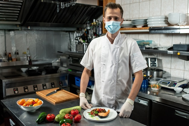 Młody profesjonalny szef kuchni w białym mundurze i masce ochronnej trzymający smażonego łososia z posiekanymi warzywami na parze na talerzu w kuchni