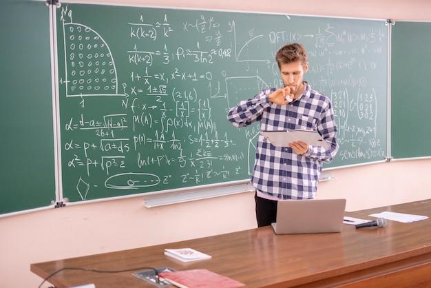 Młody profesor dowodzący twierdzenia na tablicy b