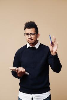 Młody profesor trzymający książkę, wyjaśniający noszenie okularów na beżowej ścianie