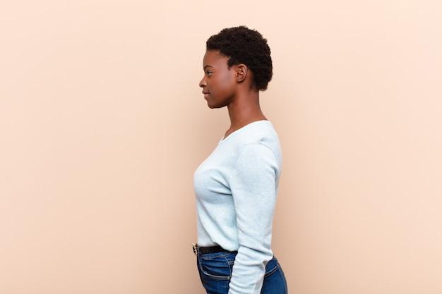 Młody profil całkiem czarny womanon widok chce skopiować przestrzeń przed sobą, myśląc, wyobrażając sobie lub marzyć