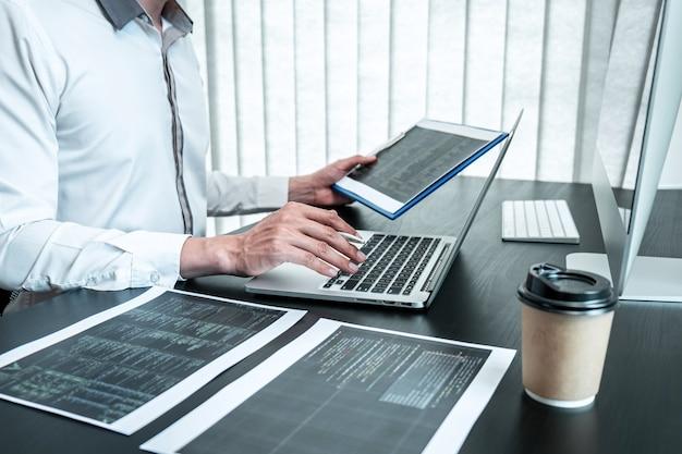 Młody programista pracujący na komputerze z oprogramowaniem javascript w biurze it. pisanie kodów i stron internetowych z kodem danych oraz kodowanie technologii baz danych w celu znalezienia rozwiązania problemu.