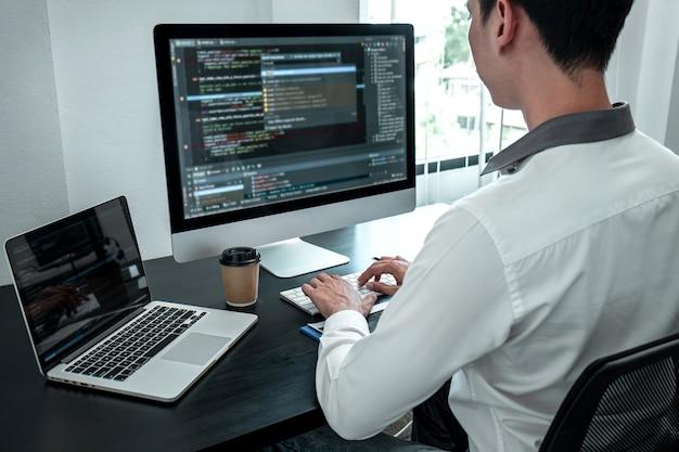 Młody programista pracujący na komputerze z oprogramowaniem javascript w biurze it