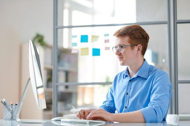 Młody programista przekonany, patrząc na monitor komputera podczas pracy przy biurku w biurze