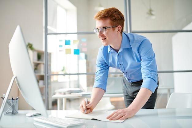 Młody programista robi notatki podczas oglądania wideo dla webdesignerów na ekranie komputera