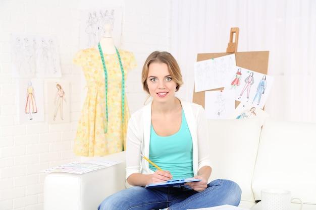 Młody projektant mody rysuje nową kolekcję szkiców