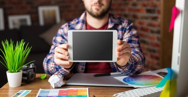 Młody projektant perspektywiczny z tabletem graficznym w nowoczesnym biurze