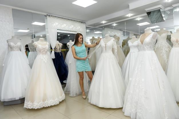 Młody projektant pozuje z manekinem w salonie ślubnym