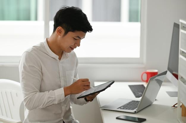Młody projektant pracujący w domu z cyfrowym tabletem