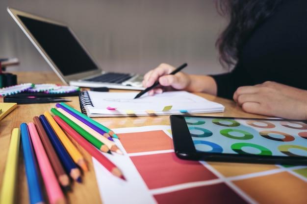 Młody projektant pracuje jako projektanci mody i rysuje szkice