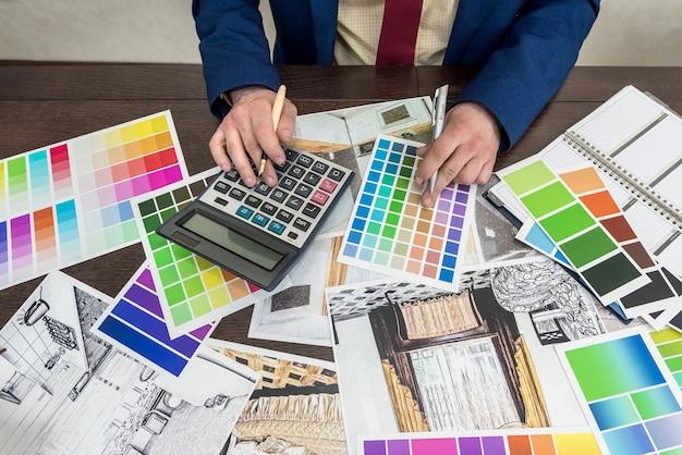 Młody projektant pracuje nad wyborem koloru i remontem nowoczesnego mieszkania. naszkicuj płaskie i kolorowe wzory na biurku w biurze