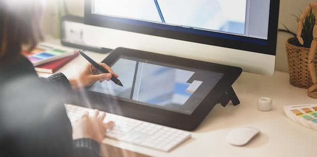 Młody projektant rysuje szkice na tablecie graficznym