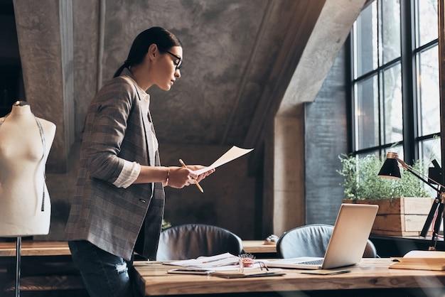 Młody projektant. skoncentrowana młoda kobieta w okularach, patrząca na szkice, opierając się o biurko w swoim warsztacie