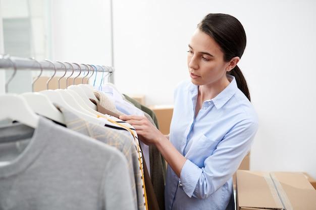 Młody projektant ubrań stojący przy wieszaku, przeglądający nową kolekcję odzieży casual
