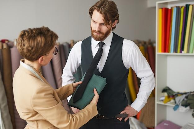 Młody projektant wybiera kolor przyszłego garnituru i omawia go z mężczyzną w warsztacie