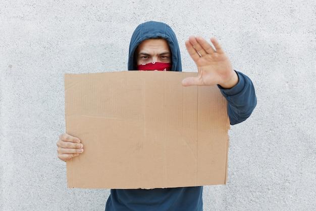 Młody protestujący mężczyzna w kapturze i zasłaniający twarz bandanami stoi przy białej ścianie trzymając karton