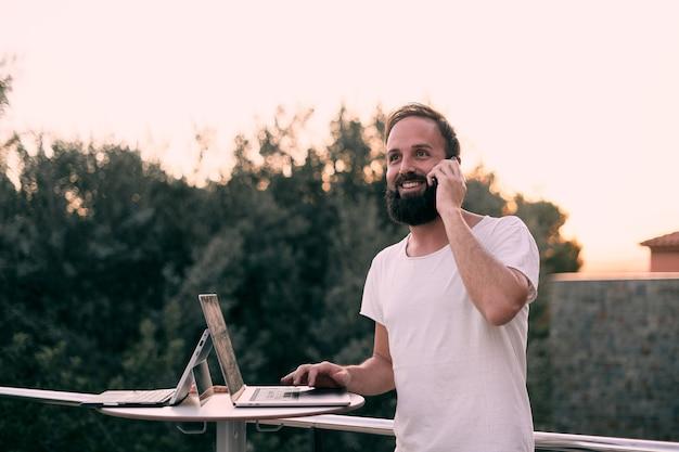 Młody przedsiębiorca odbierający spotkanie podczas pracy z tabletem w swoim leśnym domu