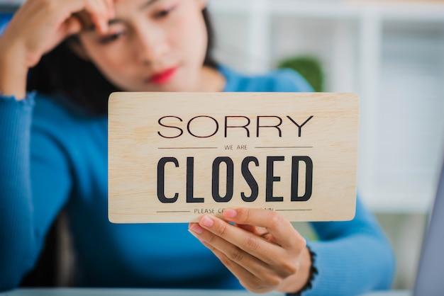 Młody przedsiębiorca początkujący przedsiębiorca mśp czuje się nieszczęśliwy, trzymając zamknięty znak.