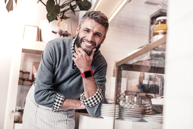 Młody przedsiębiorca. pozytywnie miły człowiek dotykający brody podczas pracy we własnej stołówce