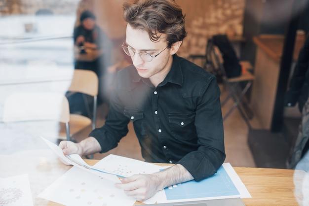 Młody przedsiębiorca pracujący w kawiarni