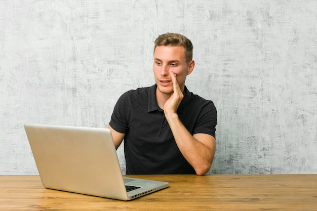 Młody przedsiębiorca pracujący ze swoim laptopem na biurku mówi tajne gorące wiadomości o hamowaniu i patrzy na bok