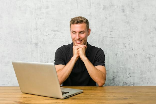 Młody przedsiębiorca pracujący ze swoim laptopem na biurku trzyma ręce pod brodą, patrzy radośnie na bok.
