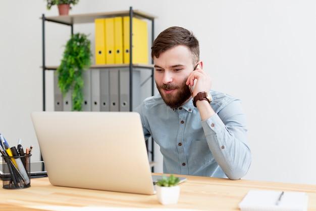 Młody przedsiębiorca pracuje na laptopie
