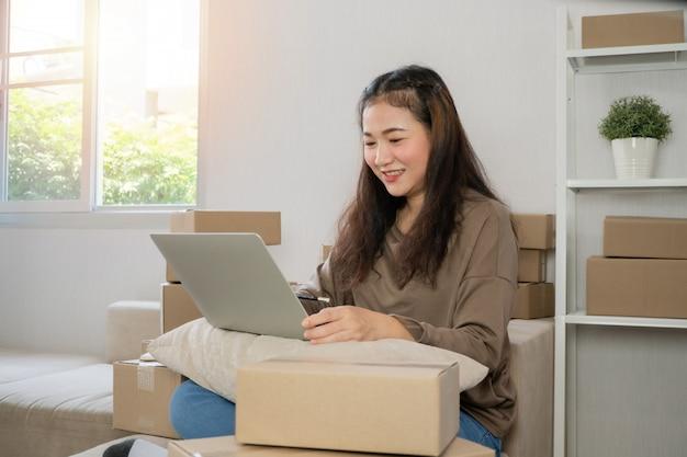 Młody przedsiębiorca, siedzący na kanapie i pracujący w domu. sprawdzanie zamówień od klientów za pomocą laptopa