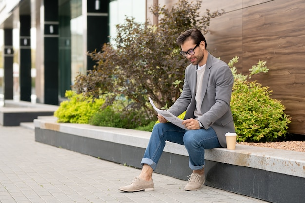 Młody przedsiębiorca w stylu smart casual siedzi w środowisku miejskim i przegląda gazety ze świeżymi wiadomościami