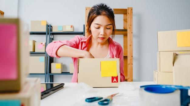 Młody przedsiębiorca z azji pakuje produkt w kartonowe pudełko do klienta, pracując w domowym biurze. właściciel małej firmy, uruchom dostawę na rynek online, koncepcja niezależnego stylu życia.
