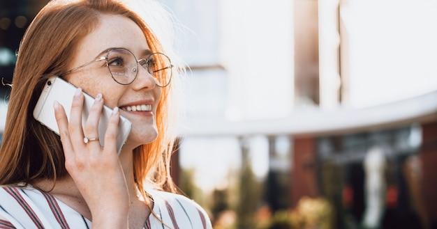 Młody przedsiębiorca z rudymi włosami i piegami w okularach rozmawia przez telefon i uśmiecha się