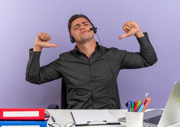 Młody, przekonany, blondynka pracownik biurowy mężczyzna na słuchawkach siedzi przy biurku wskazuje na siebie