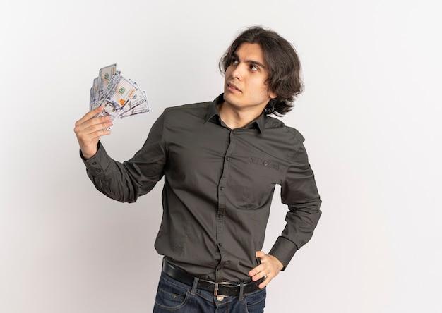 Młody, przekonany, przystojny kaukaski mężczyzna trzyma pieniądze i patrzy na bok na białym tle na białym tle z miejsca na kopię