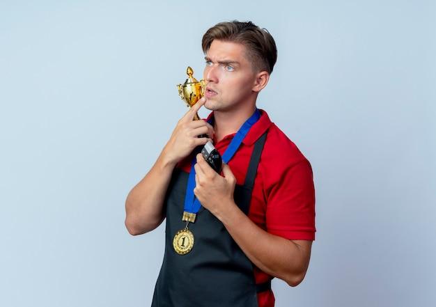 Młody przemyślany blond męski fryzjer w mundurze ze złotym medalem trzyma puchar zwycięzcy i maszynkę do strzyżenia włosów patrząc z boku na białym tle na białej przestrzeni z miejscem na kopię