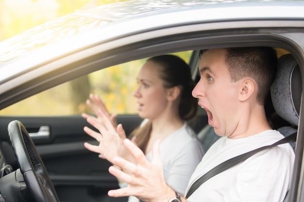 Młody, przerażony kierowca i kobieta pasażerka