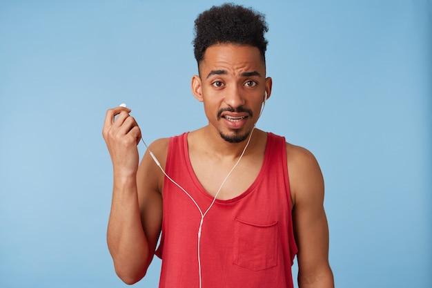 Młody przesłuchujący, czarnoskóry atrakcyjny facet słucha muzyki, nosi czerwoną koszulkę, nie słyszy, o czym mówi, wyciąga jedną słuchawkę, wstaje.