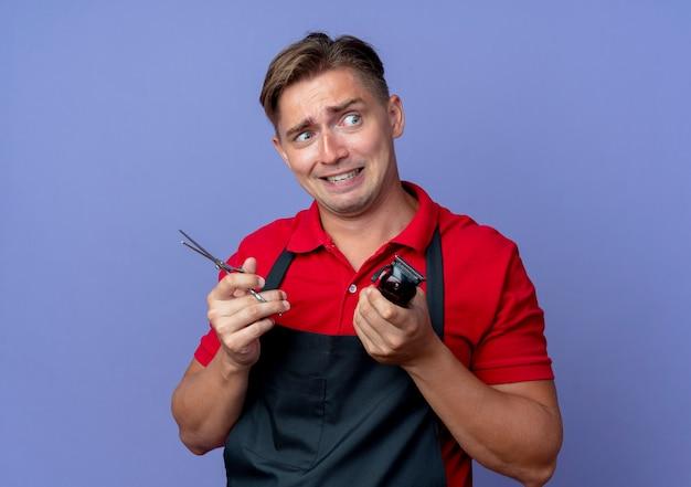 Młody przestraszony blond mężczyzna fryzjer w mundurze trzyma nożyczki i maszynkę do strzyżenia włosów, patrząc na bok na białym tle na fioletowej przestrzeni z miejsca na kopię