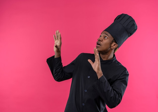 Młody przestraszony kucharz afroamerykański w mundurze szefa kuchni udaje, że broni się rękami odizolowanymi na różowej ścianie
