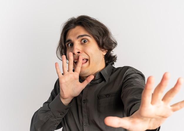 Młody przestraszony przystojny kaukaski mężczyzna udaje, że broni się rękami na białym tle