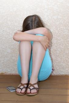 Młody przygnębia nastoletniego siedzącego na podłodze