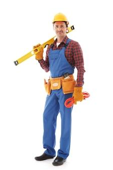 Młody przyjazny pracownik fizyczny z narzędziami na białym tle