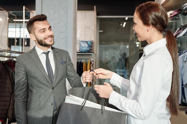 Młody przyjazny sprzedawca mijający papierowe torby z nowymi ciuchami do szczęśliwego biznesmena w eleganckim garniturze w butiku