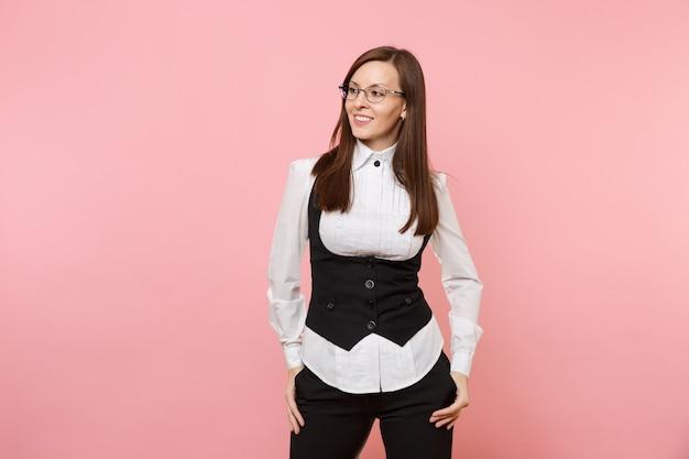 Młody przyjemny biznes kobieta w garniturze i okularach, trzymając ręce w kieszeniach, patrząc na bok na białym tle na pastelowym różowym tle. szefowa. koncepcja bogactwa kariery osiągnięcia. skopiuj miejsce na reklamę.