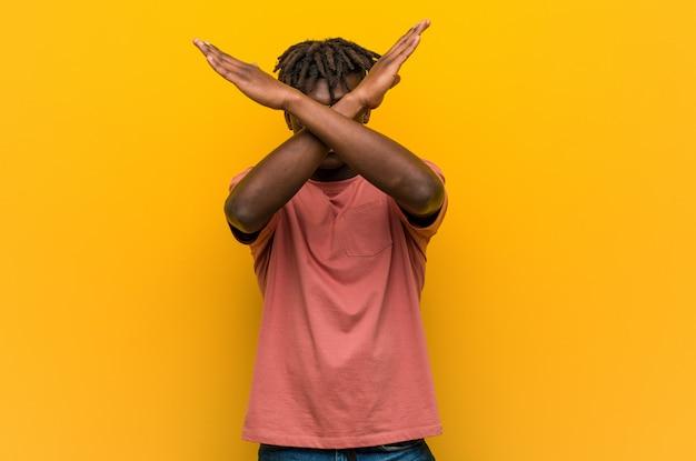 Młody przypadkowy czarny człowiek nosi okulary przeciwsłoneczne, trzymając dwie ręce skrzyżowane