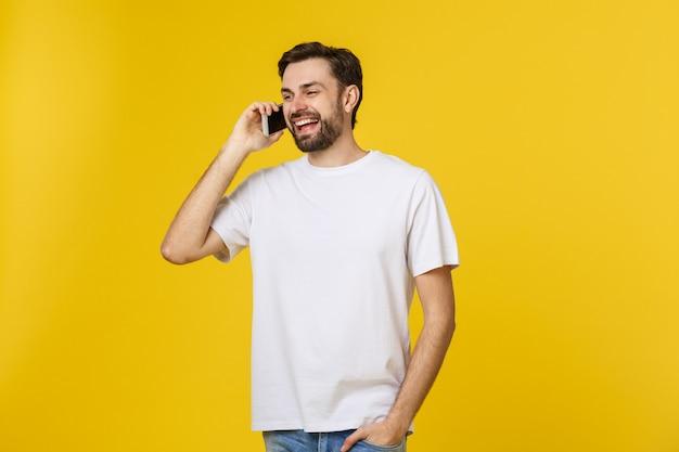 Młody przypadkowy mężczyzna rozmawia przez telefon na białym tle