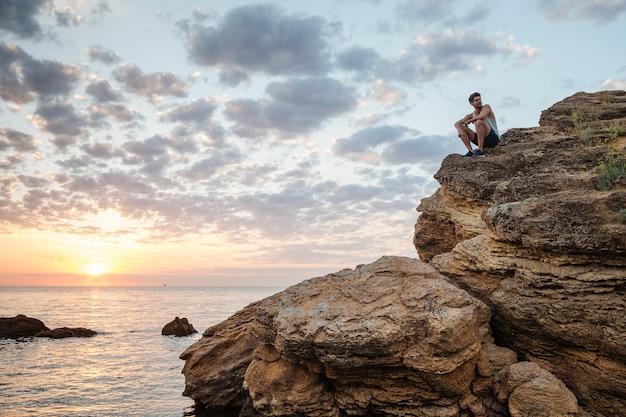 Młody przypadkowy mężczyzna siedzący na górskiej skale nad morzem i patrzący na zachód słońca