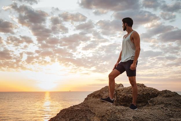 Młody przypadkowy mężczyzna stojący na górskiej skale nad morzem i patrzący na zachód słońca