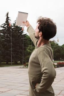Młody przypadkowy mężczyzna stojak i seansu notepad