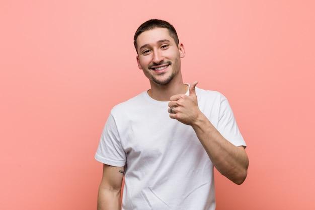 Młody przypadkowy mężczyzna uśmiecha się kciuk up i podnosi